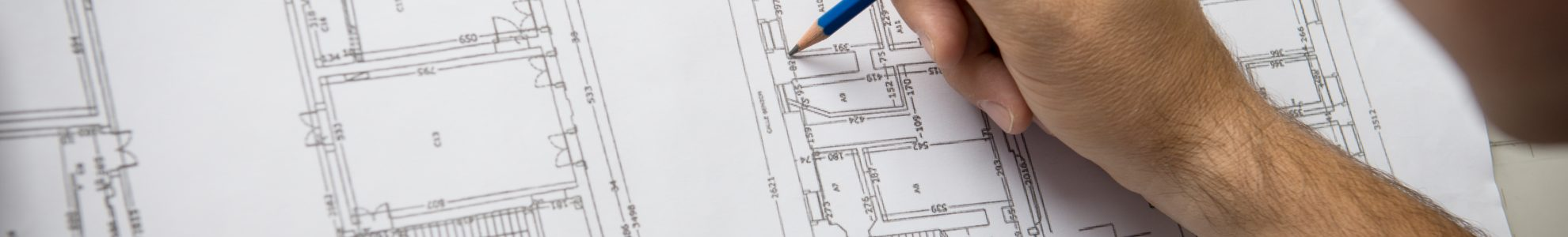 Closeup Of Male Architect Working On Blueprint At Office.